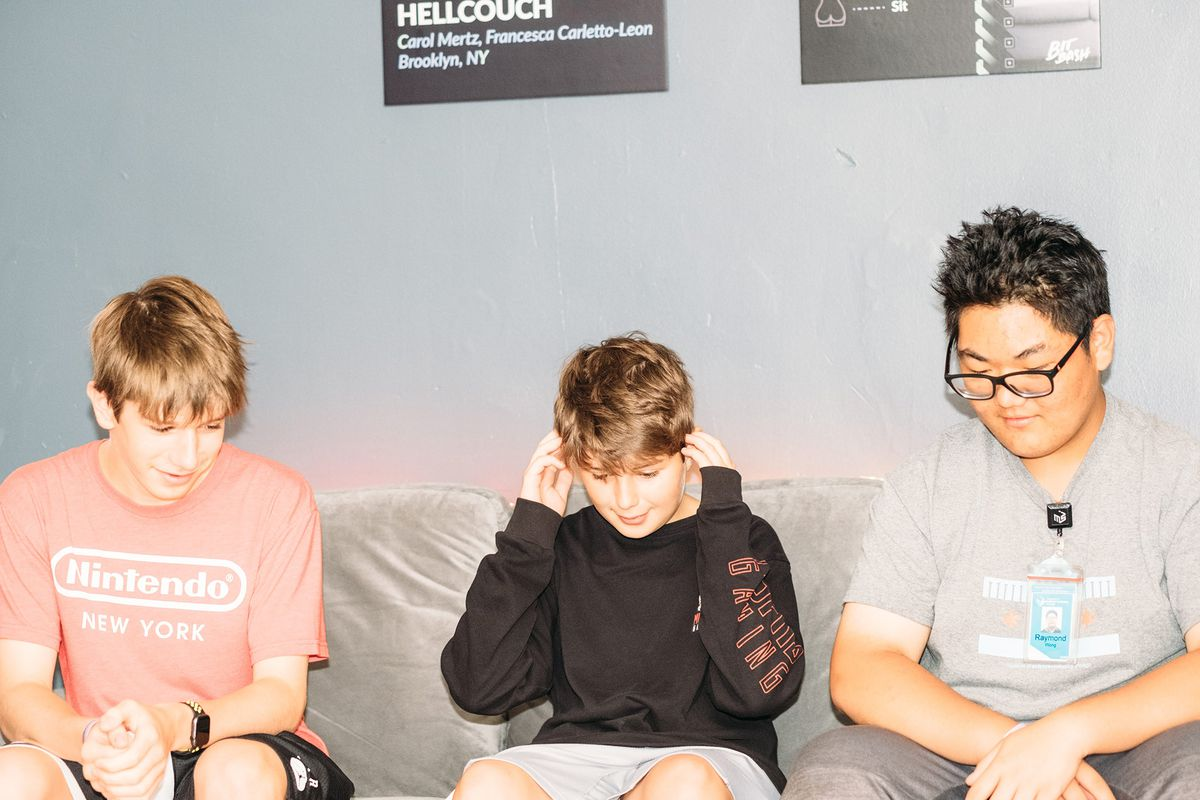Three high-school aged kids listen to a talking sofa while LED lights illuminate them from behind. Bit Bash at the Museum of Science and Industry, 2019.