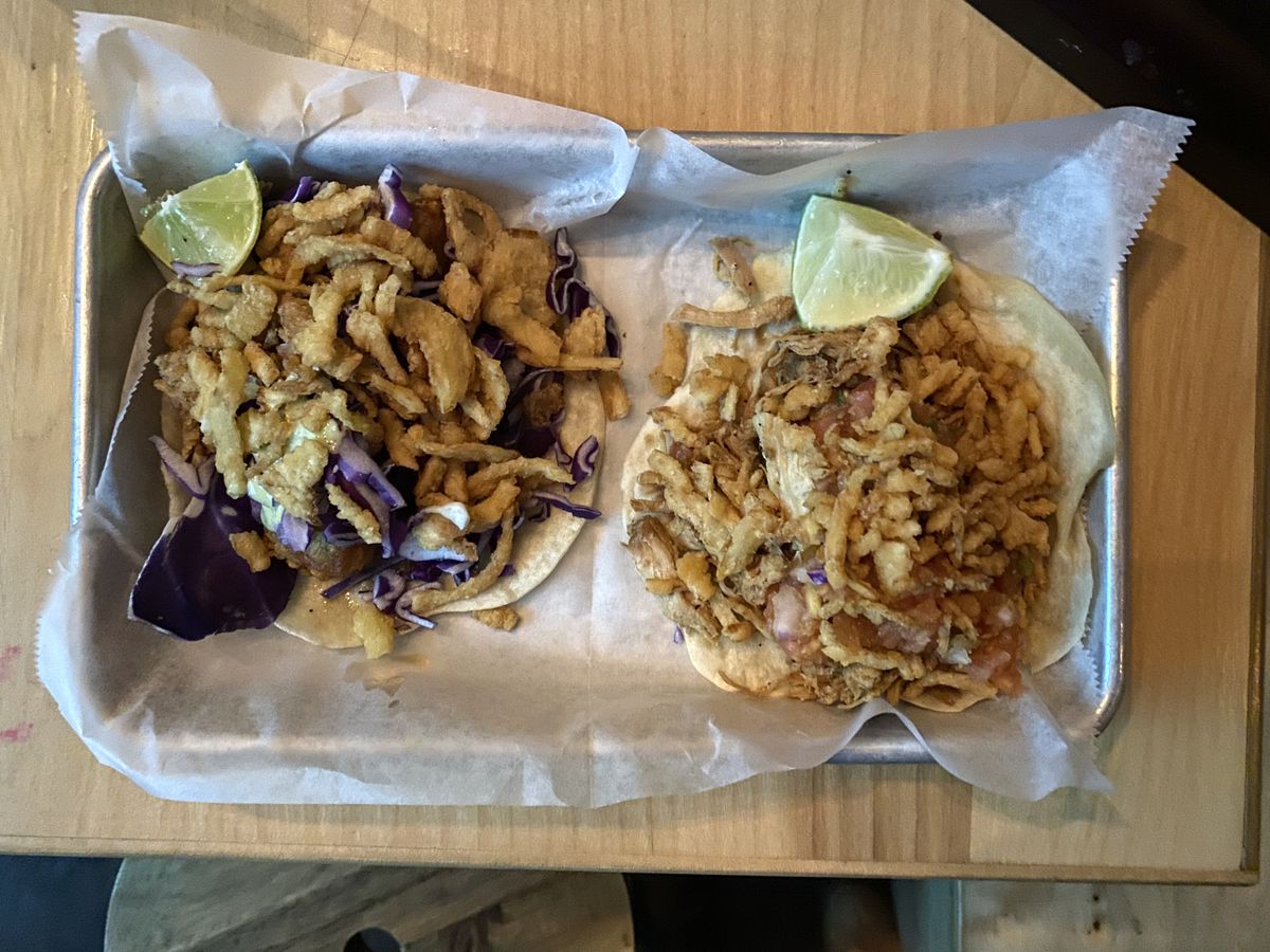Fried spam and chicken adobo tacos sit on wax paper on a metal tray at Swell Dive