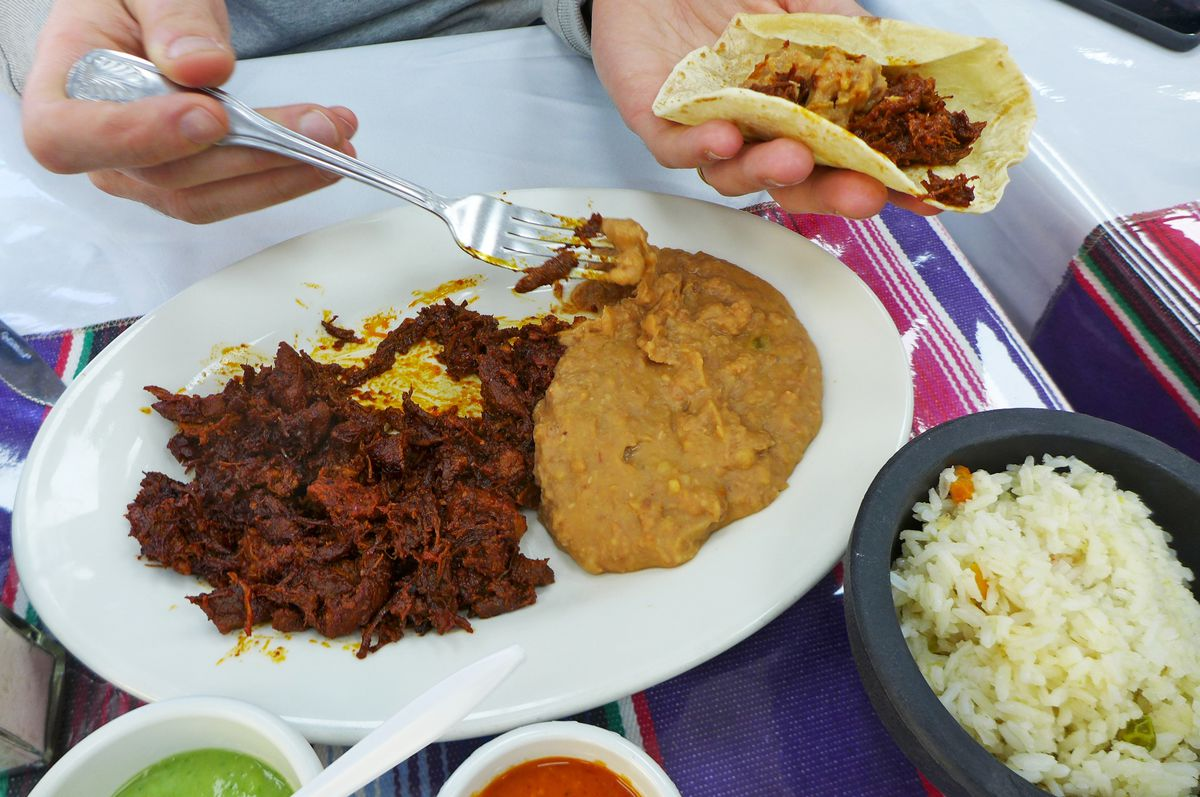 A platter with a dense red beef stew on the left and pool of beige refried beans on the right.