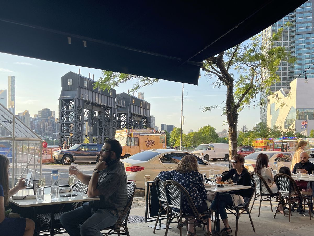 Customers are seated on the sidewalk at an outdoor dining area, with views of a busy street and a city skyline in the background