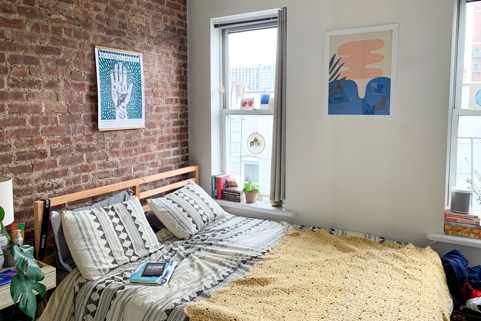 A bedroom with exposed brick, two windows, and a large bed.