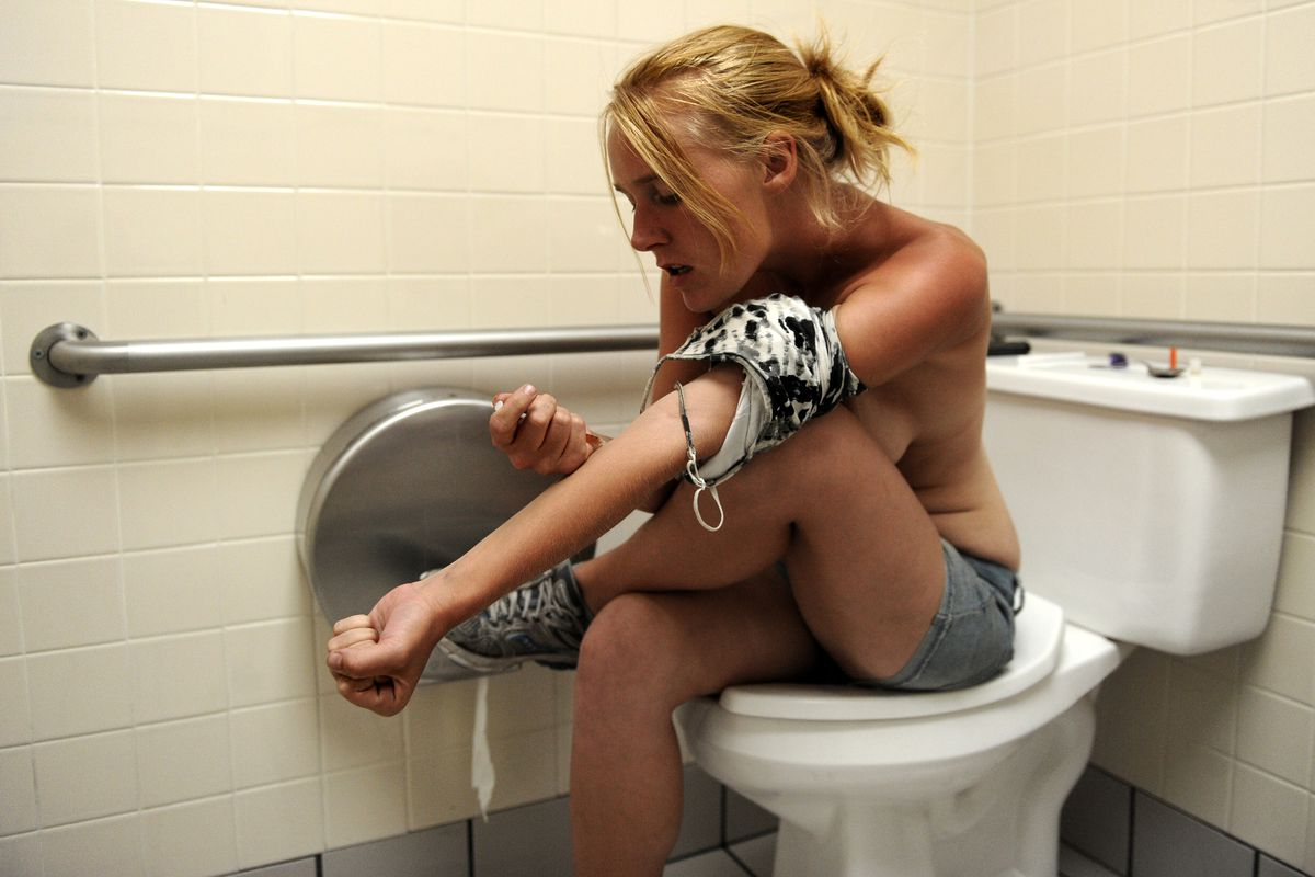 A homeless woman in Denver shoots up heroin.