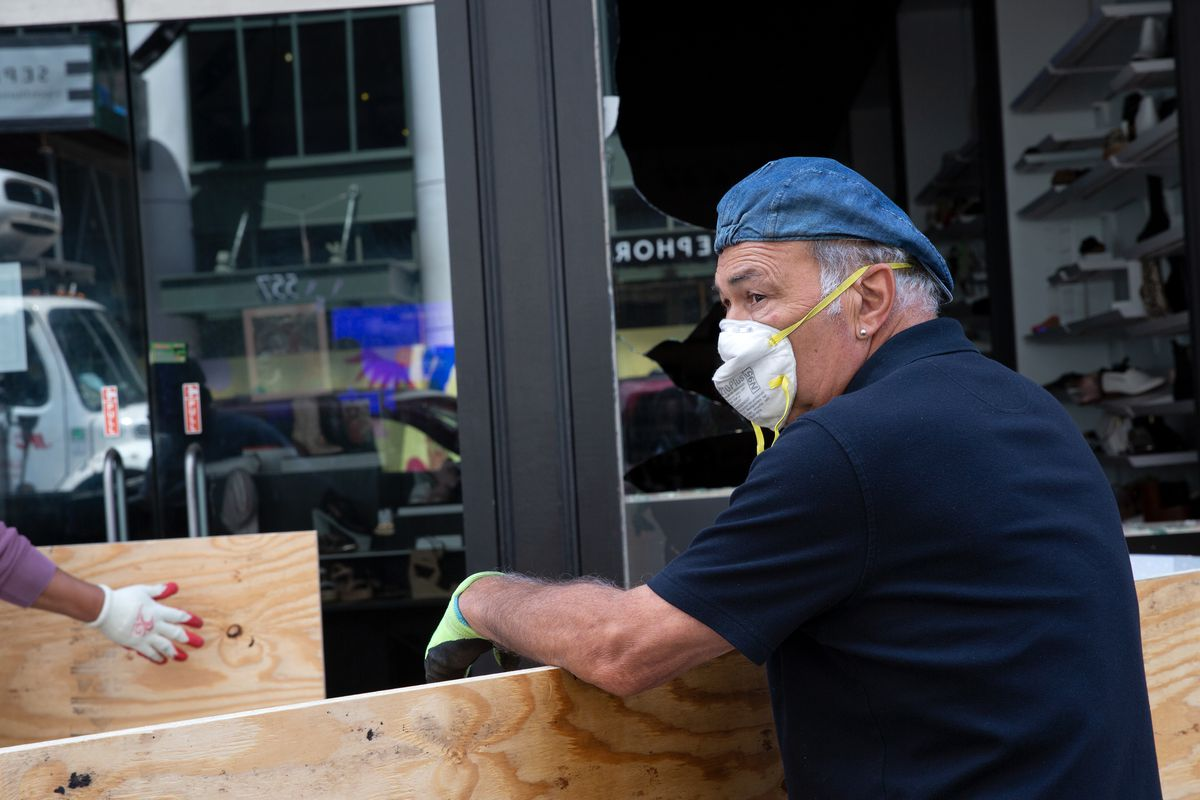 Workers repair damage to a SoHo shoe store.