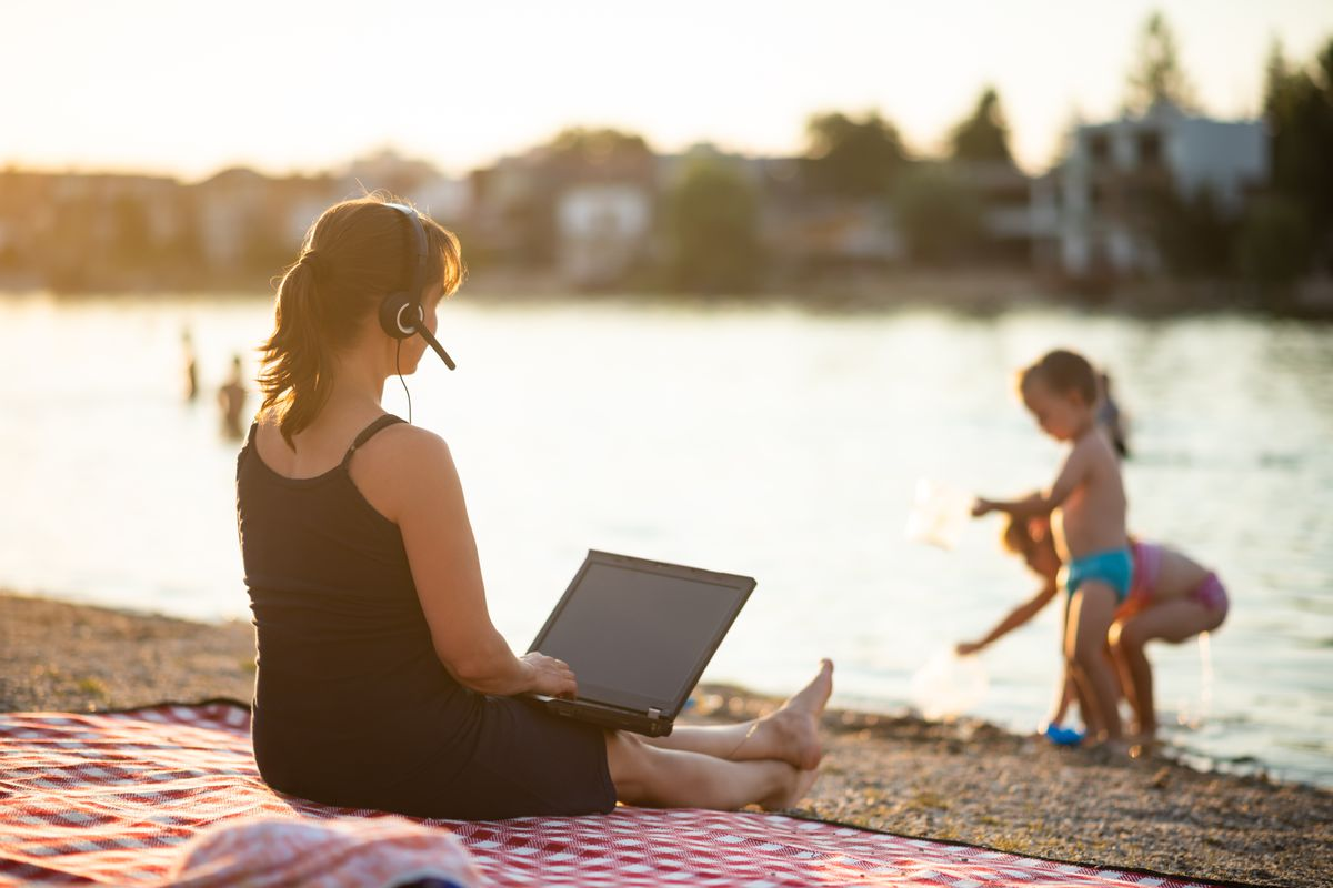 A woman sits on a blanket at the shore while working on her laptop computer and watching her children play near the water.