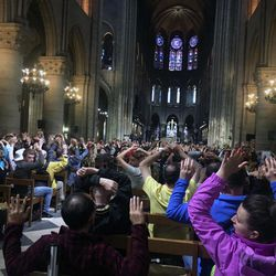 """In this image provided by Nancy Soderberg, people inside Notre Dame cathedral sit with their hands in the air, after an attack on police in Paris, Tuesday, June 6, 2017. Paris prosecutors have opened a counterterrorism investigation after an unidentified assailant attacked police with a hammer outside Notre Dame Cathedral. French Interior Minister Gerard Collomb says the attacker cried """"it's for Syria"""" as he went after officers patrolling an esplanade in front of the famous landmark. (Nancy Soderberg via AP)"""