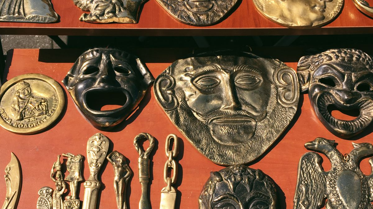 An array of copper masks are displayed on top of a red surface.