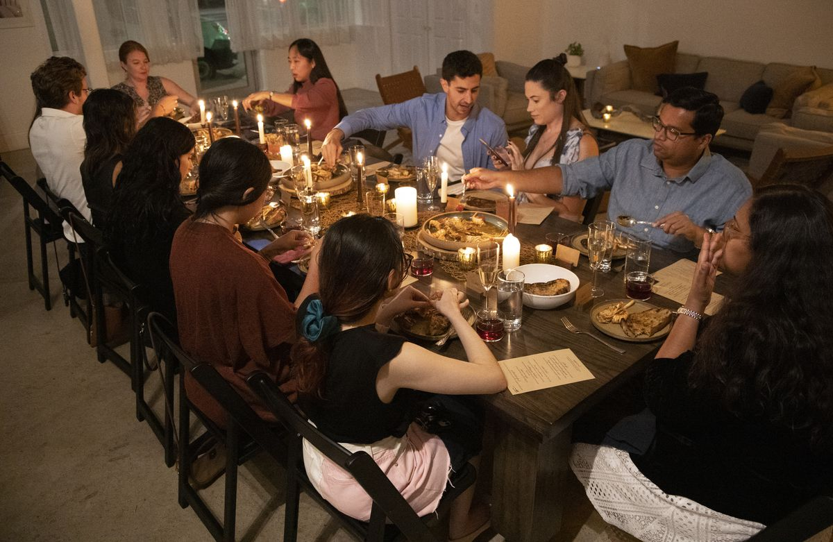 14 people seated around a dinner table.