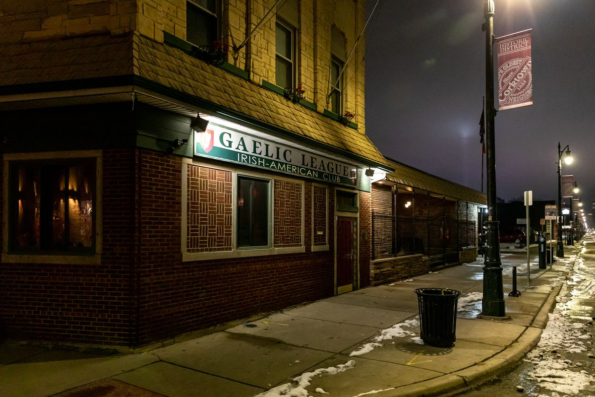 The exterior of the Gaelic League is lit by lamps along Michigan Avenue on a cold winter night with some snow frozen to the ground.