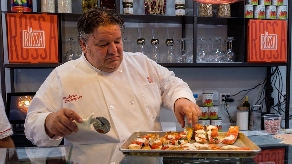 Chef Stefano Callegari standing over a tray of pizza at La Rossa