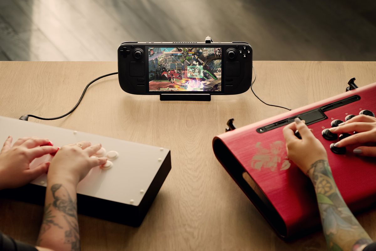 two people playing Guilty Gear Strive with two fight sticks connected to a Steam Deck