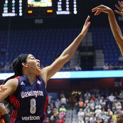 Connecticut Sun's Jasmine Thomas (5) follows through on a jumper of Washington Mystics' Bria Hartley (8).