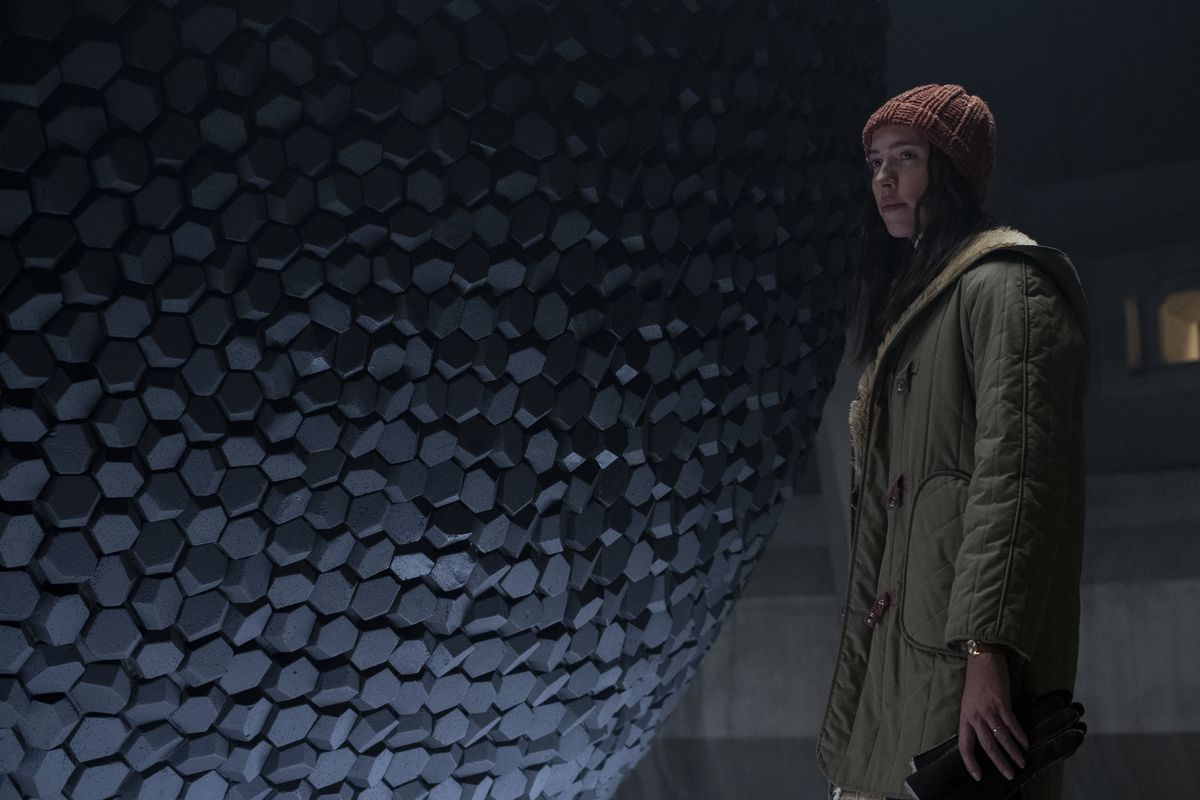 A woman, the daughter of the director and the inheritor of the lab upon his death, stands in front of an amorphous sphere made of dark gray stones.