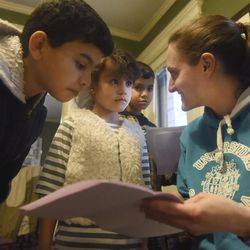 In this Wednesday, Jan. 18, 2017, Chelsea Krieger with the United Congregation Church works with Al Kalaf children Mohammad, 12, foreground, Rasha 6, and Abdul, 8, on their homework at their home in Manchester, Conn.