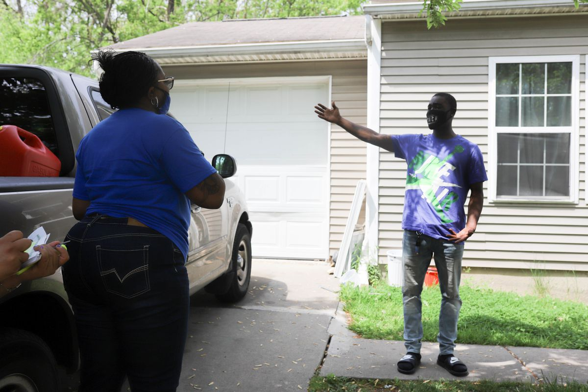 A woman in a blue shirt with a clipboard stands in a driveway next to a truck, as a man wearing a purple, green and white Nike Air shirt speaks emphatically with her.