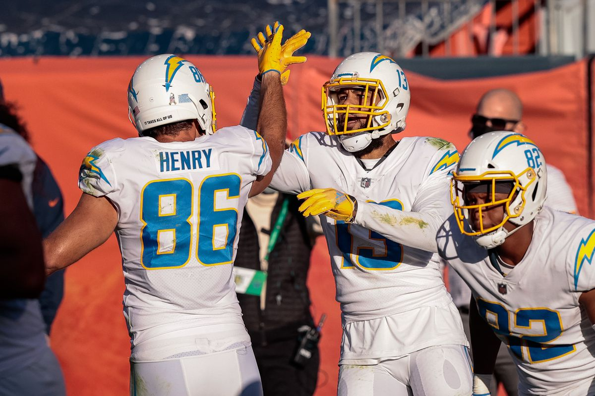 Los Angeles Chargers wide receiver Keenan Allen (13) celebrates with tight end Hunter Henry (86) after scoring a touchdown against the Denver Broncos in the second quarter at Empower Field at Mile High.