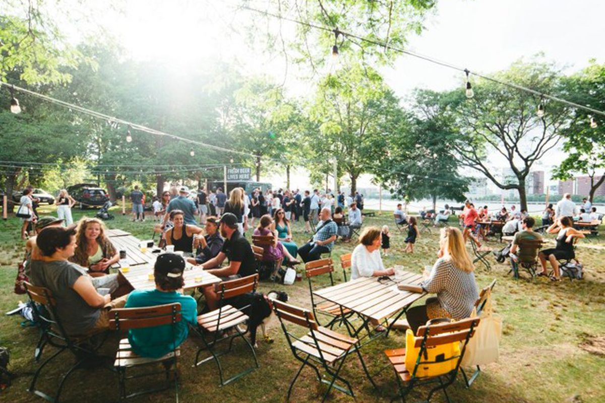 People sit at wooden tables and chairs in a tree-lined park on a sunny summer day