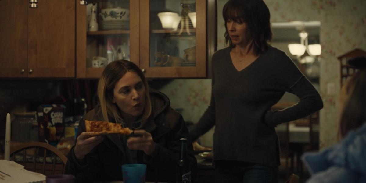 a photo of mare of easttown played by kate winslet eating a slice of pizza and drinking a beer while her friend looks on