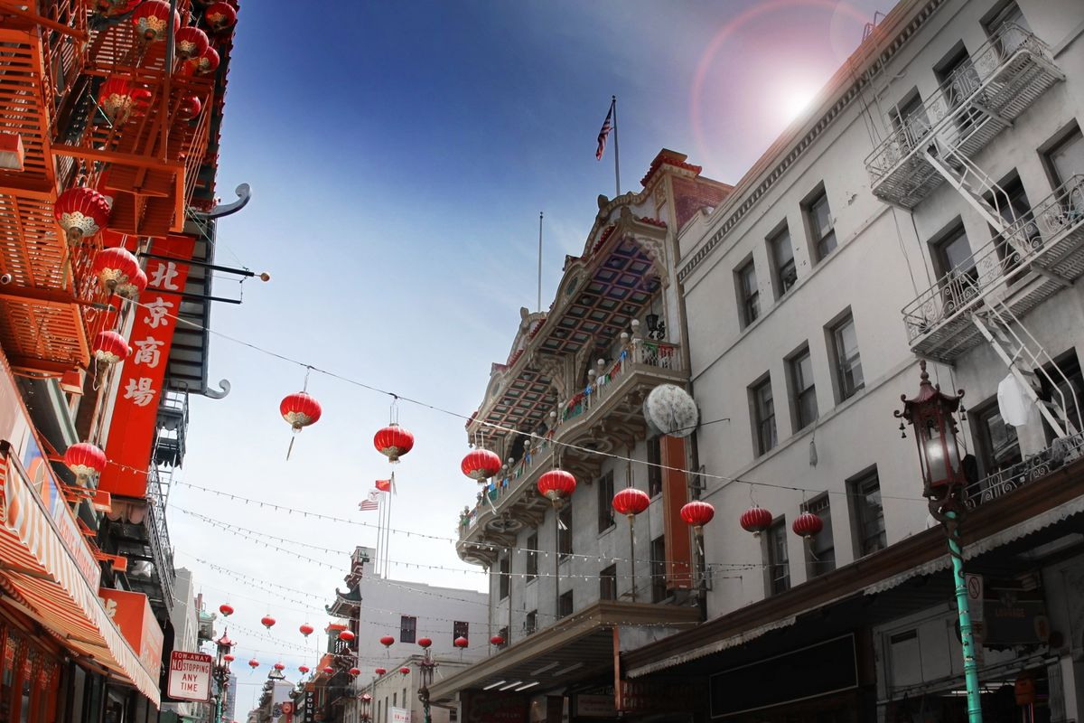 Lanterns hanging between two buildings in a Chinatown alley.