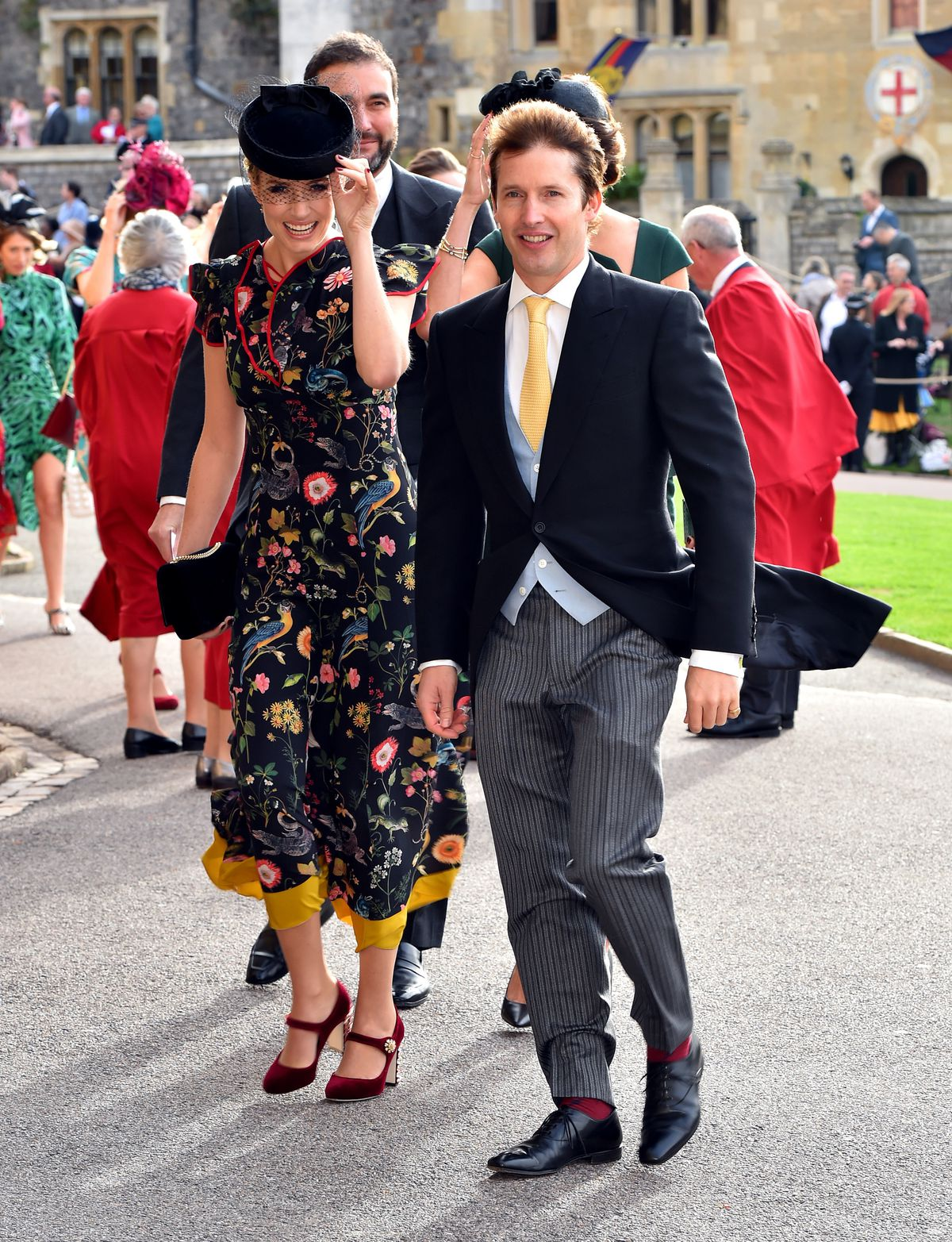 James Blunt arrives wearing a navy and gray suit and a yellow tie.