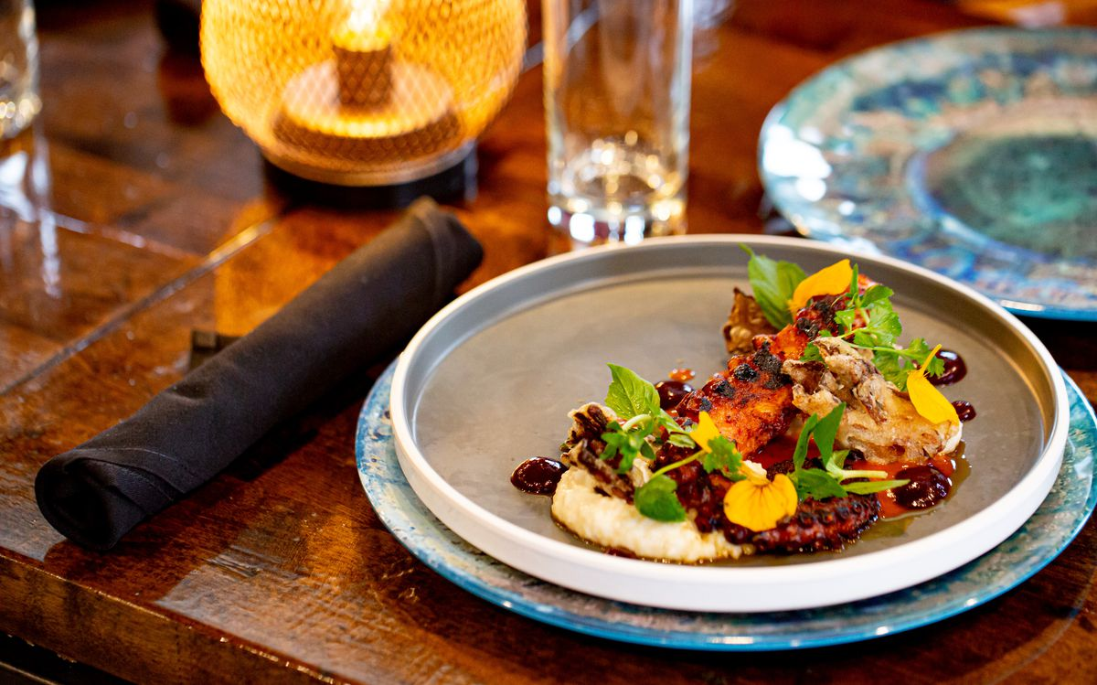 A white stoneware plate with barbecue octopus garnish with popcorn rice grits, maitake mushrooms, red cabbage puree, and chili butter