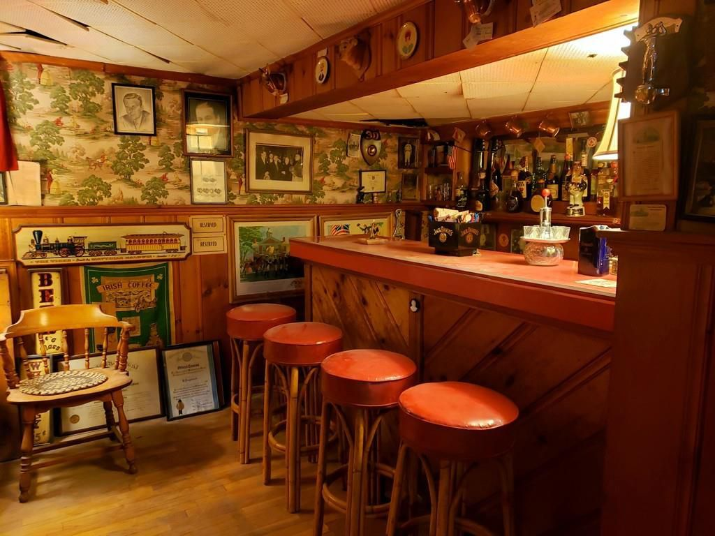 A cozy home pub with stools in front of the bar and lots of stuff on the walls.