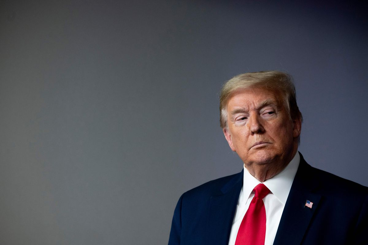 A portrait of Trump in a dark blue suit, white shirt, and bright red tie. Lit by the press room's spotlights, he frowns.