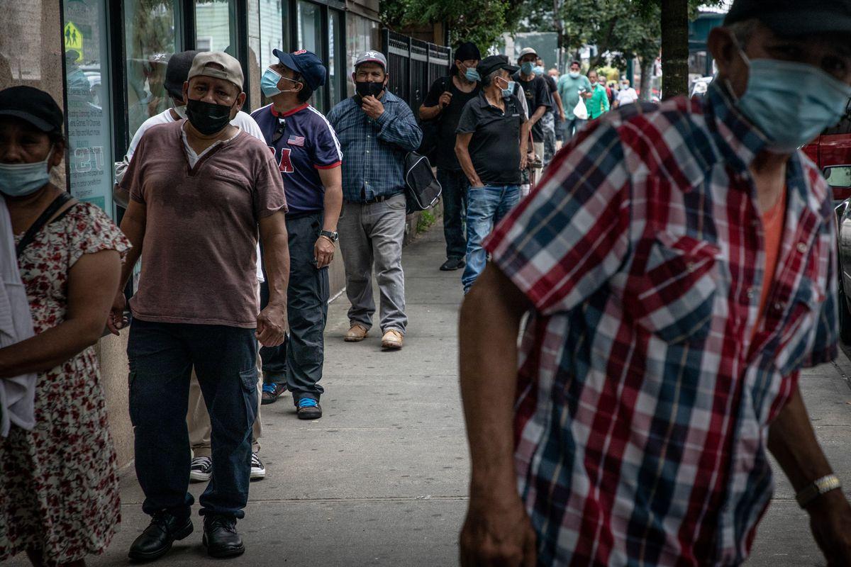 Men wait in line for food in Corona, Queens