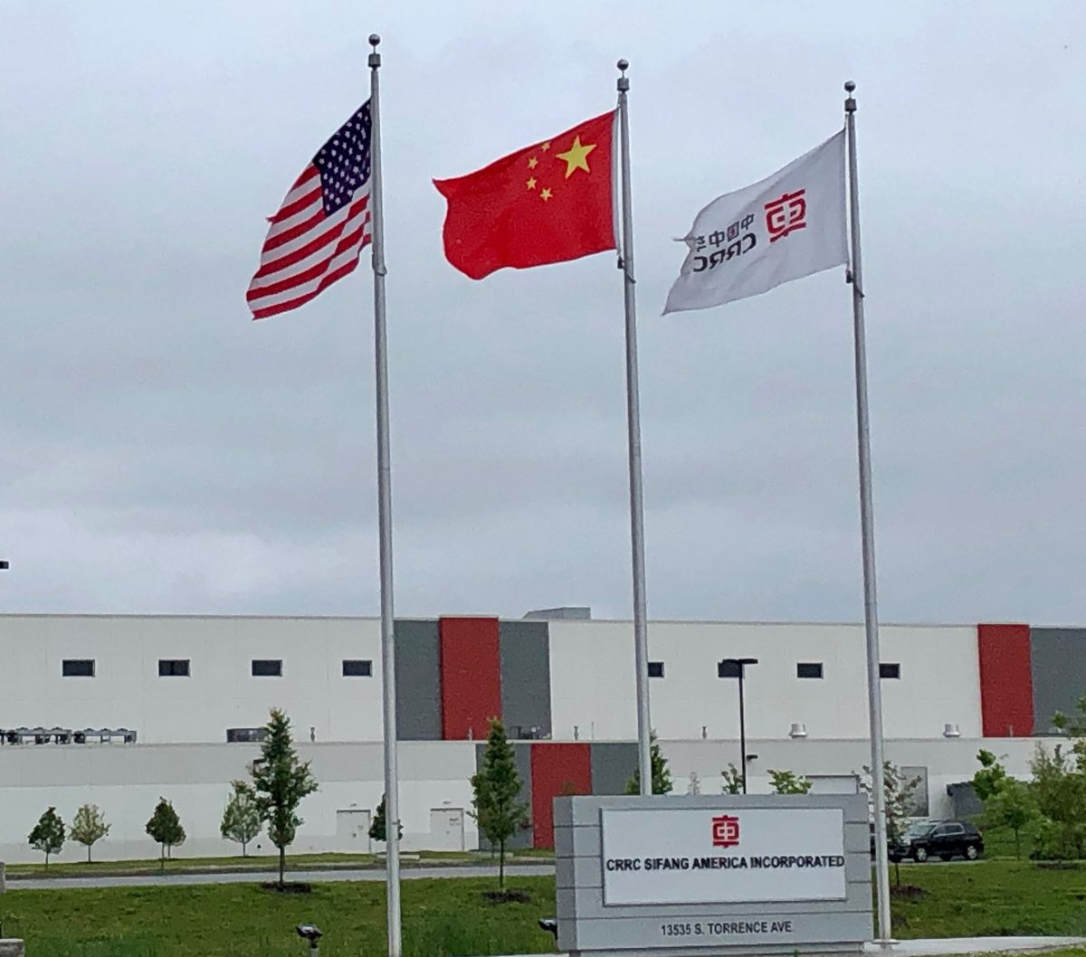 Three flags fly in front of the CRRC Sifang American plant on the South Side of Chicago.