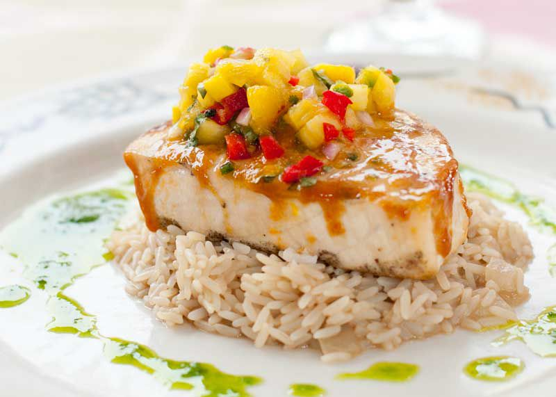 Halibut steak with a mango chutney sits on a bed of rice.