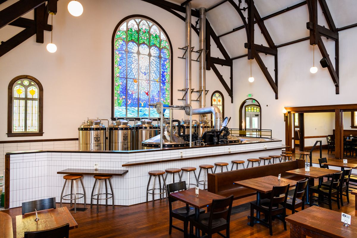 Wooden tables with pews as banquettes lead up to the white tile barrier between the brewing equipment and the seating area, with stools along the barrier.