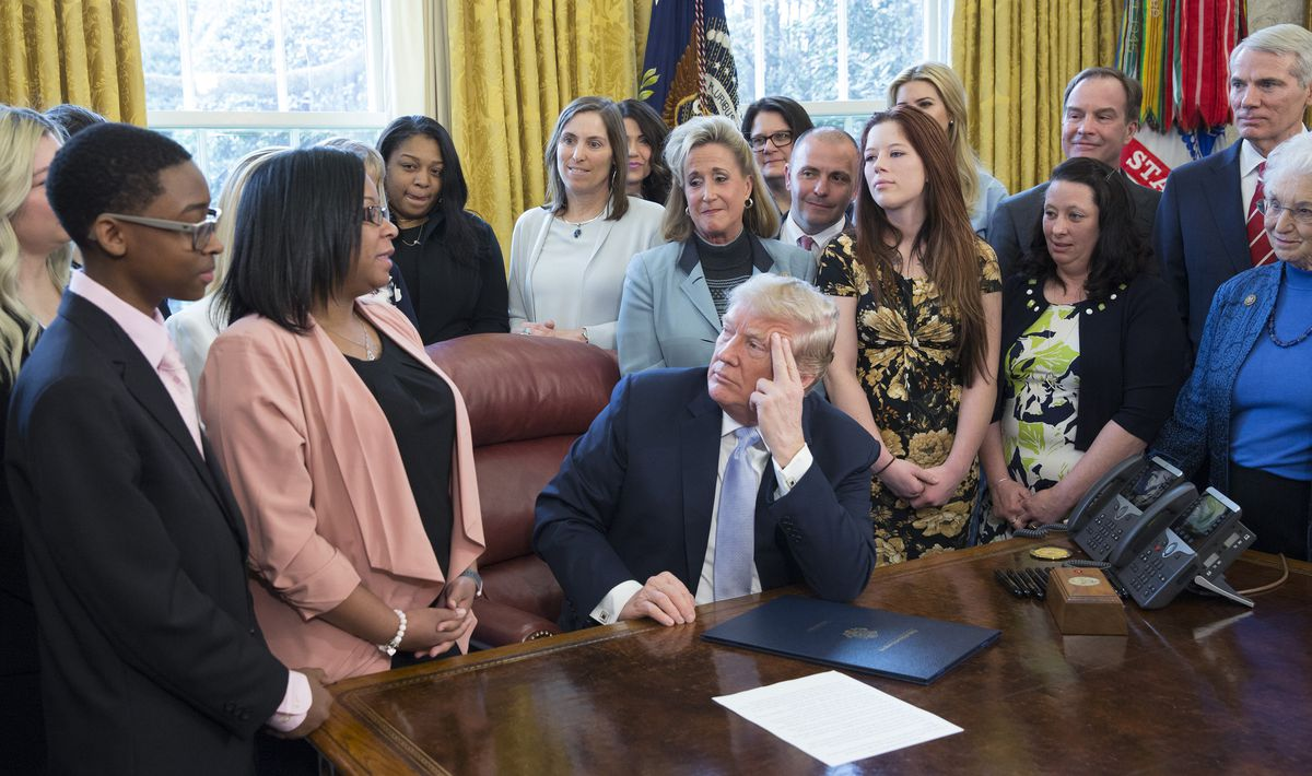 Yvonne Ambrose of Chicago talks to President Donald Trump before he signed a bill intended to curb sex trafficking. Ambrose's daughter was killed after a pimp offered her up on Backpage.com., a website that has been criticized for including ads for prosti