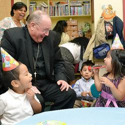 Archbishop Timothy Dolan shares a laugh at a birthday party. He also leads the U.S. Conference of Catholic Bishops.