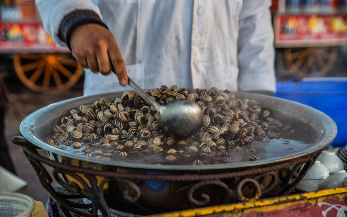 a large ladle stirs a bowl of snail soup.
