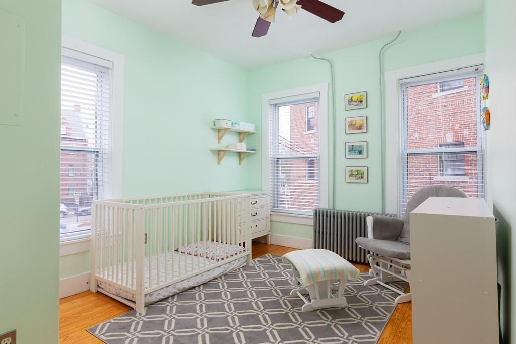 A bedroom with three windows and crib.