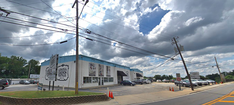 A white and blue textiles building near a highway with clouds above.