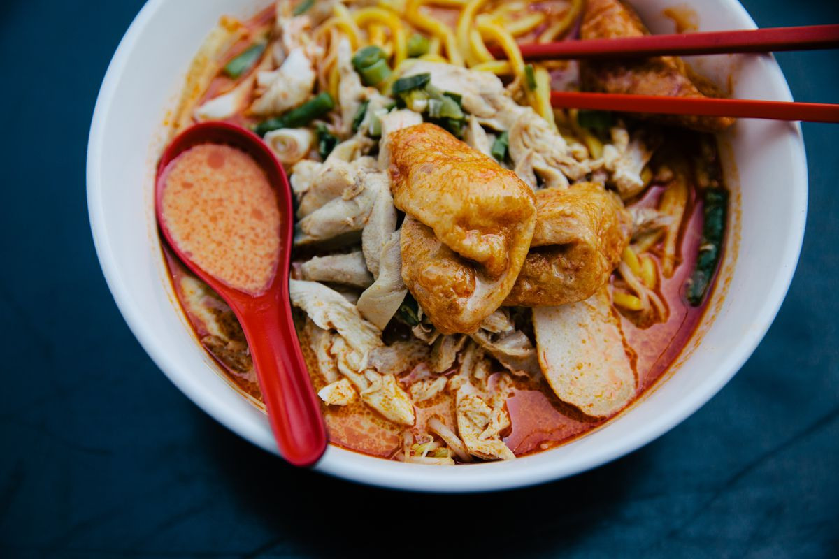Fiery red broth bobs with noodles in a classic laksa