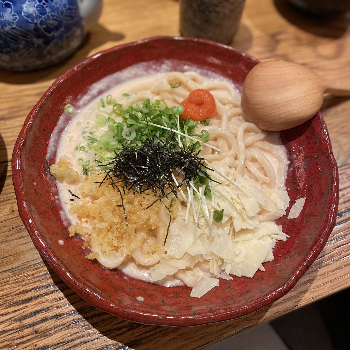 Mentai creamy sauce udon topped with green onions, slivers of seaweed, and pieces of tempura batter from Udon Mugizo in Japantown