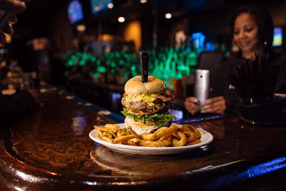 A massive towering burger held together precariously by a steak knife and surrounded by onion rings and fries on a bar as a woman takes a photo on her cellphone.