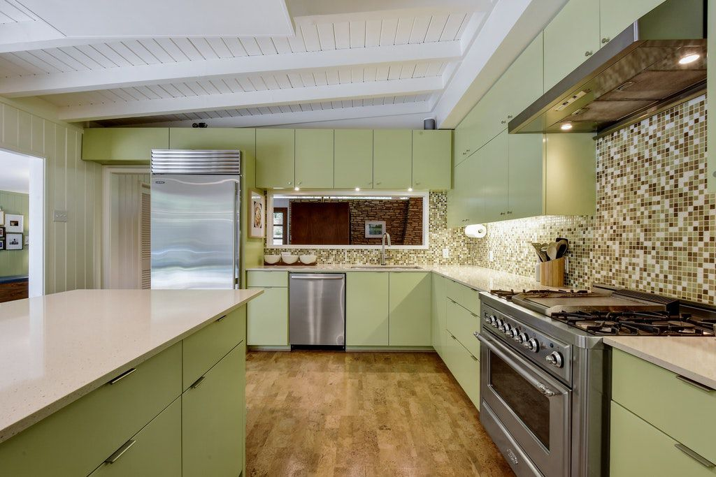 A kitchen features light green cabinets, wood floors, and silver appliances.