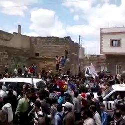 In this image made from amateur video released by the Shaam News Network and accessed Thursday, April 19, 2012, Syrians surround UN vehicles during a demonstration in Daraa, Syria. In Syria on Thursday, activists said regime forces took control of a southern town and shot at activists in another soon after international observers left. Protesters chanted anti-government slogans for the observers to hear.