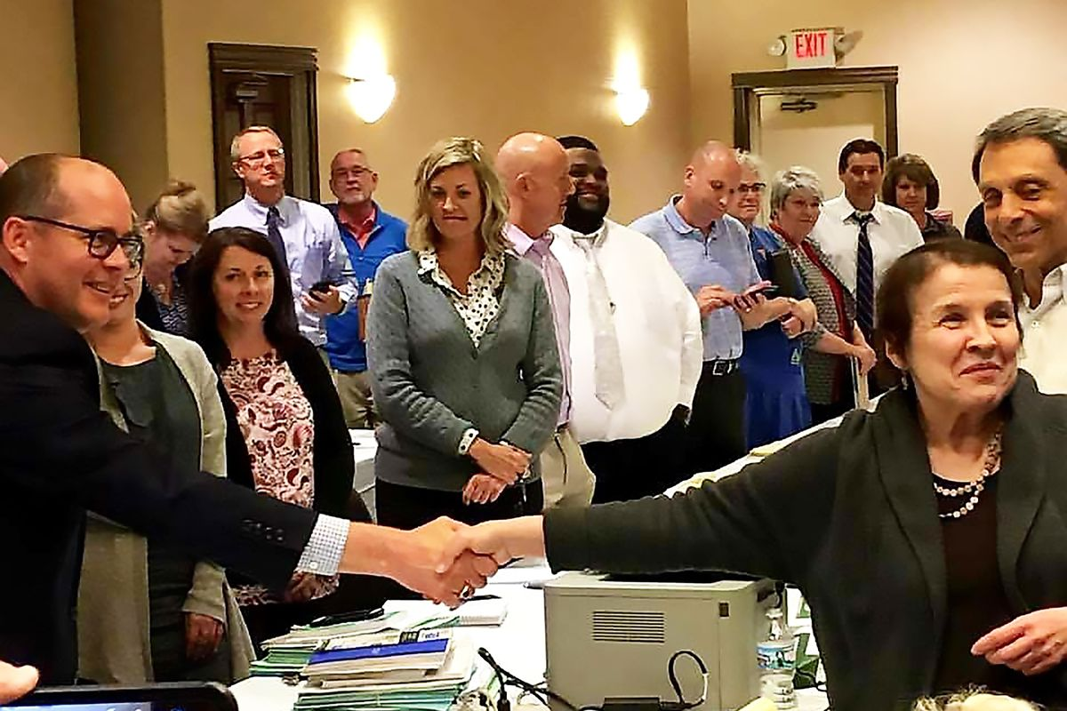 Robb Craddock, chief negotiator for the state of Illinois, and Roberta Lynch, executive director of AFSCME Council 31, shake hands over a tentative contract agreement Friday.
