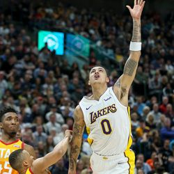 Los Angeles Lakers forward Kyle Kuzma (0) is charged with an offensive foul against Utah Jazz guard Dante Exum (11) during the game at Vivint Smart Home Arena in Salt Lake City on Tuesday, April 3, 2018.