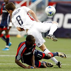 New England Revolutions' Kheli Dube, bottom, goes down while battling for the ball with Real Salt Lake's Will Johnson in the first half of an MLS soccer game, Sunday.