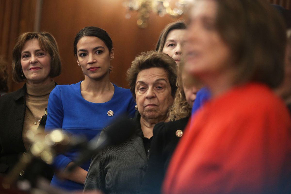 Rep. Alexandria Ocasio-Cortez in a group listening to House speaker Nancy Pelosi speak at a press conference.