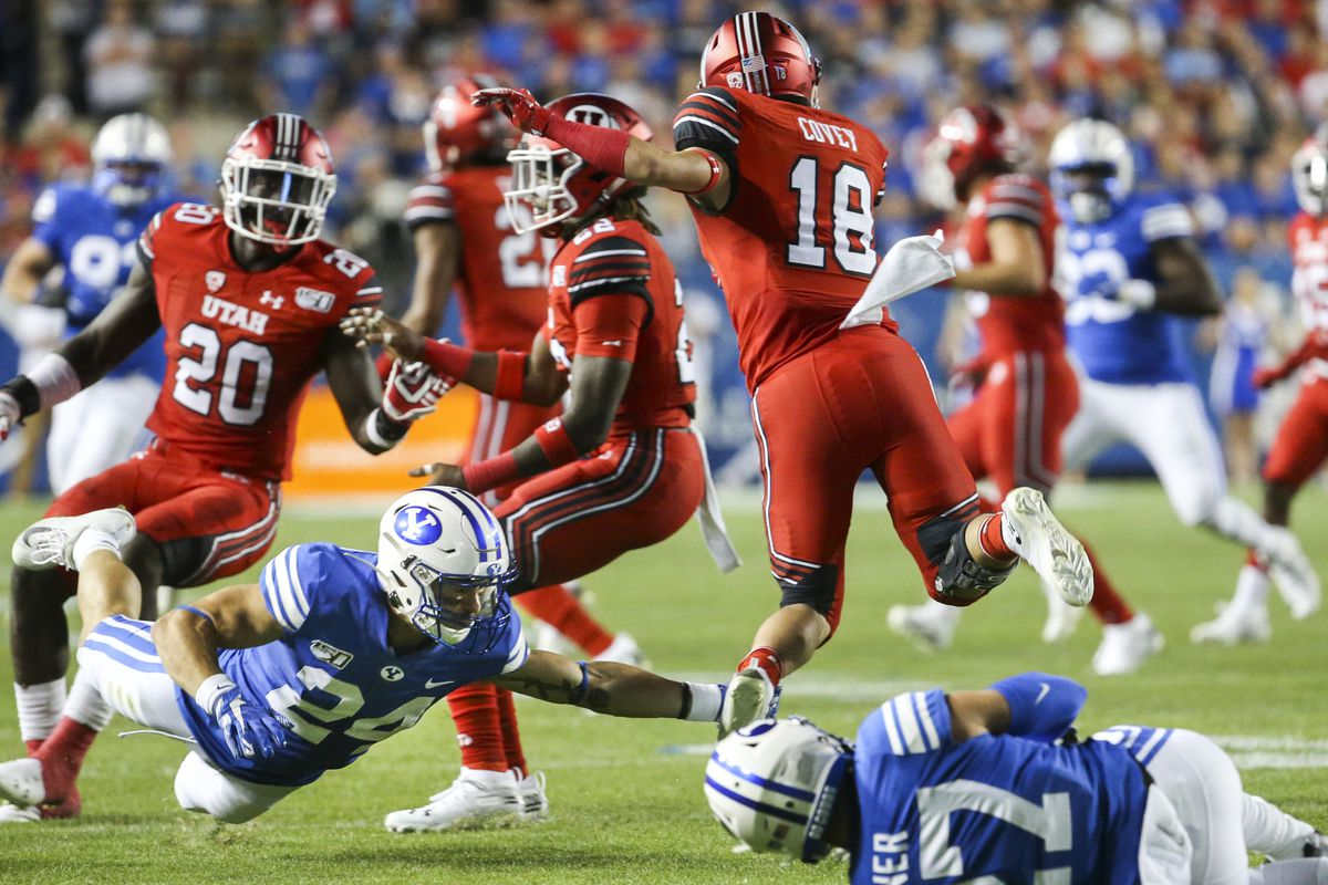 Utah wide receiver Britain Covey (18) is tripped up by BYU defensive back Austin Kafentzis (24).