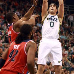 The Utah Jazz's Enes Kanter shoots over the Washington Wizards' Kevin Seraphin and Nene during a basketball game at the EnergySolutions Arena in Salt Lake City on Saturday, Jan. 25, 2014. The Jazz won 104-101.