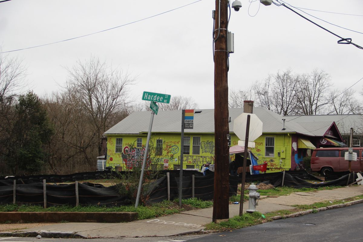 A photo of a yellow house behind a utility pole from the corner.