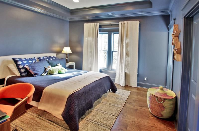 A dark blue bedroom with a  blue and tan bed.