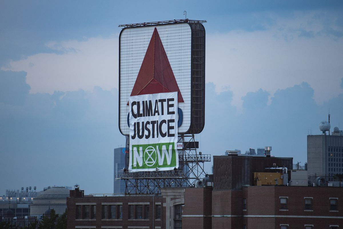 "A protest banner with the words ""Climate Justice Now"" placed in front of the Citgo sign in Kenmore Square in Massachusetts."
