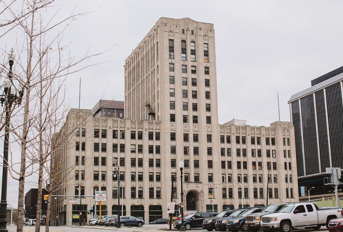 The exterior of the Old Detroit Free Press building. The facade is tan with multiple windows.